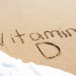 Vitamin D written in the sand with foam from a wave washing up