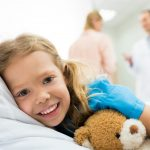 happy kid lying on hospital bed while mother talking with doctor